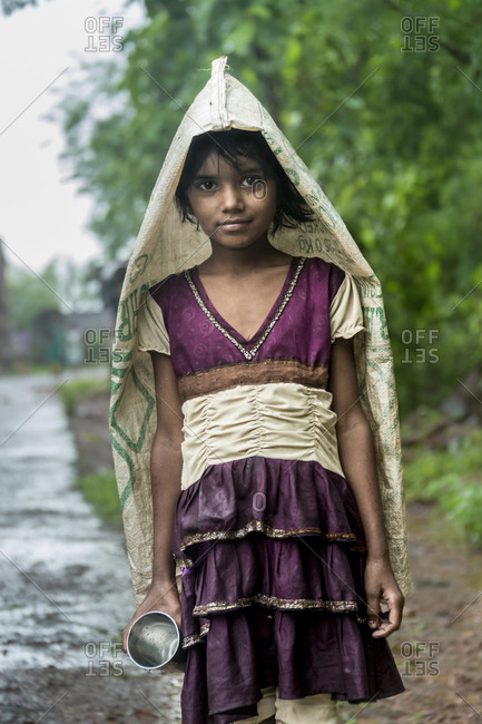 India - July 31, 2014: Young girl using a bag to cover herself from the rain