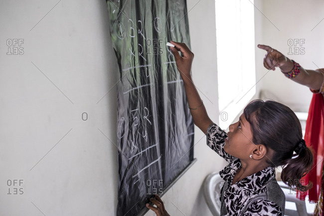 India - July 31, 2014: Girl writing on a makeshift blackboard in a rural school