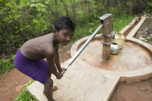 Central India - August 1, 2014: Boy pumps water from a well