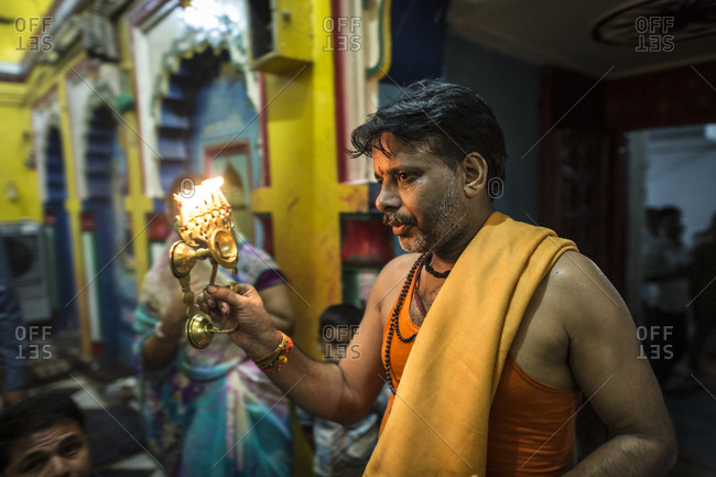 Central India - August 1, 2014: Priest offers worship at a Hindu temple