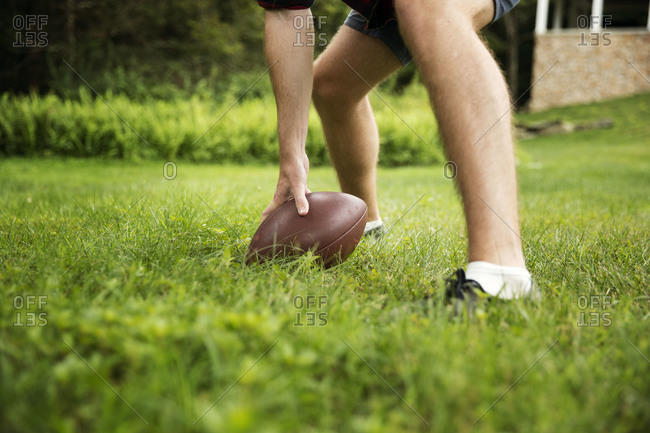 Close up of a person hiking an American football