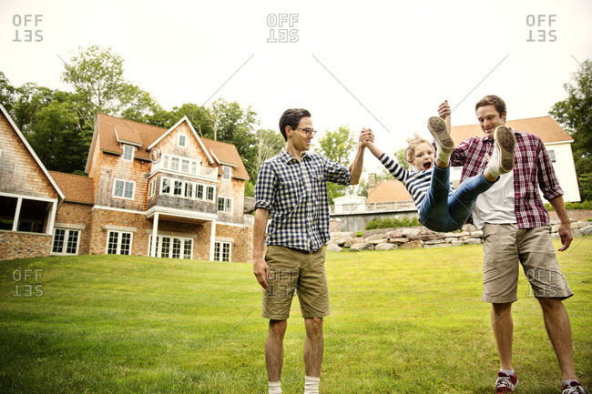 Fathers swinging their daughter