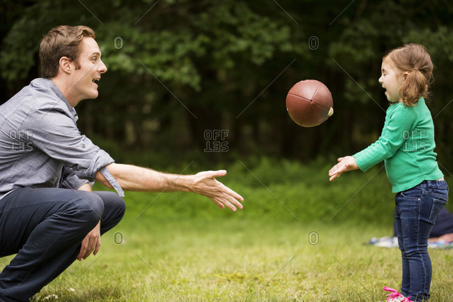 Father and daughter passing an American football