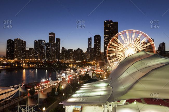 Chicago, IL, USA - September 16, 2014: Illuminated ferris wheel with skyscrapers in background, Chicago