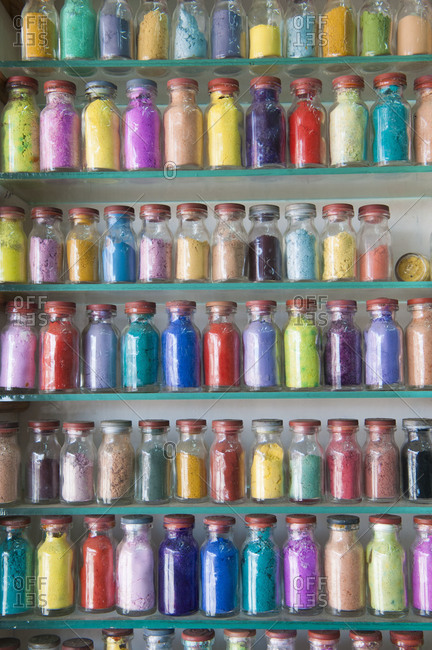 Jars of colored paint on shelves in market