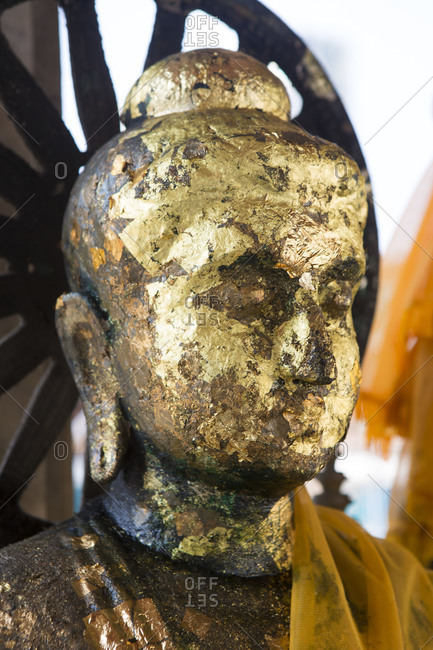 The gold-leaf head of an ancient statue of the Buddha