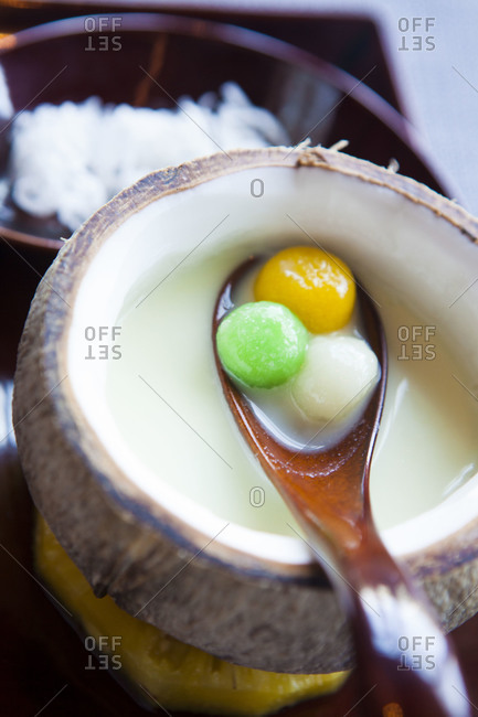 Spoon bringing melon balls out of coconut
