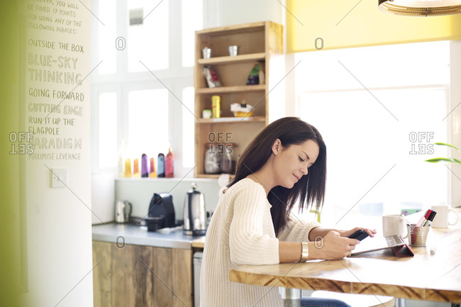 Woman looking at phone in office space