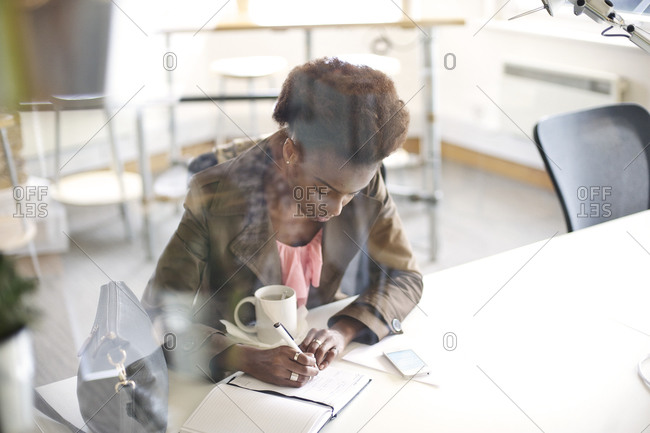 A woman taking notes at work