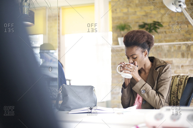 A woman sipping from a mug at work