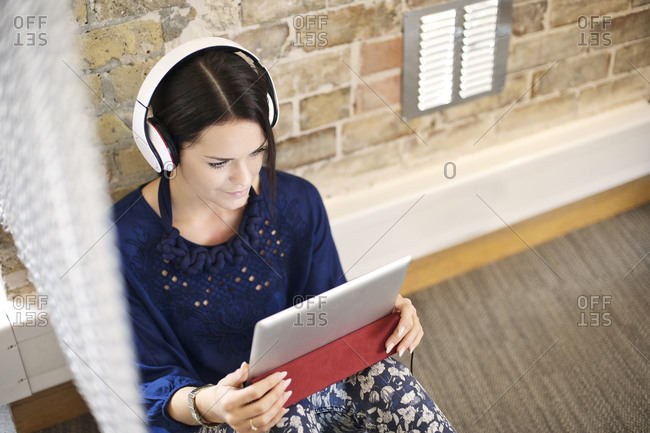 A woman listening to a tablet
