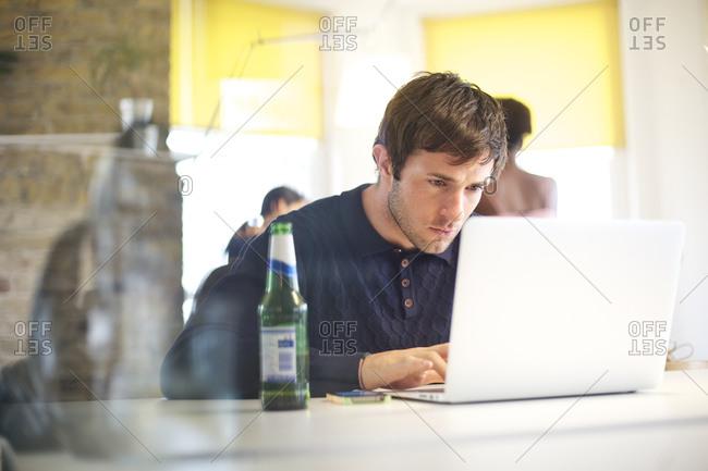 A man at his desk reading his computer