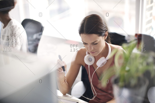 Woman with headphones concentrating at desk