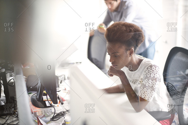 A woman looking closely at her office computer