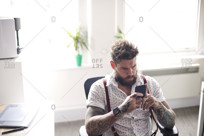 Man reading phone at office desk