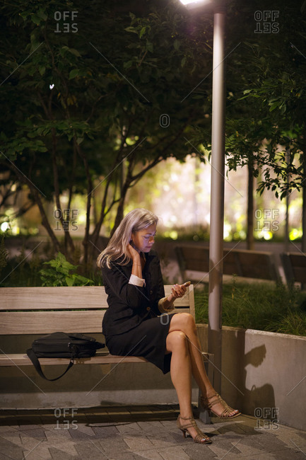 A business woman on a park bench at night