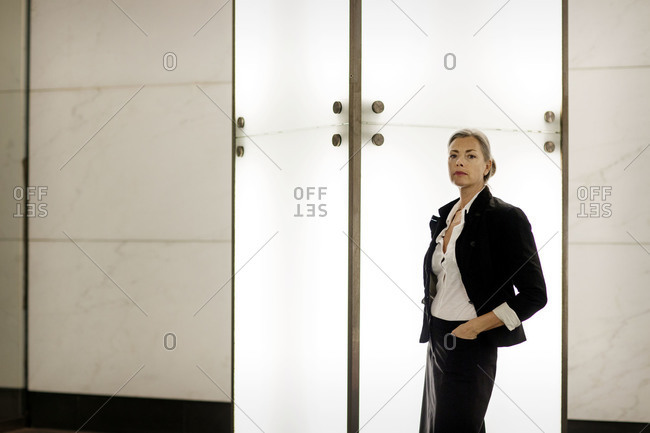A woman stands in bright lobby