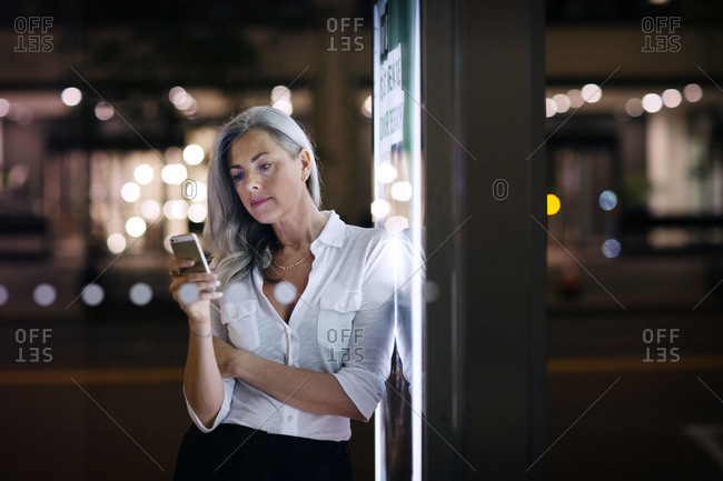 Woman leaning against sign reading her phone