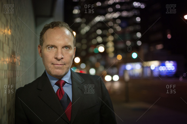 Businessman leaning against a wall in city