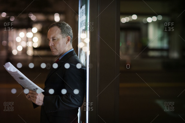 Man leaning against sign reading newspaper