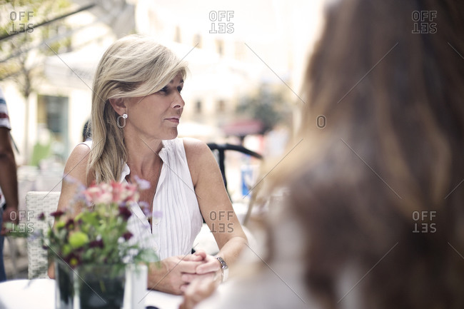 Two women sitting at street cafe