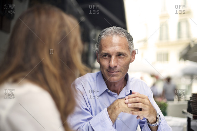 Middle-aged man sitting at street cafe with a brunette woman