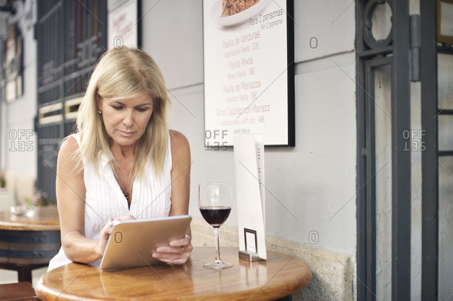 Woman sitting at street cafe and using her tablet