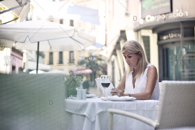 Woman using her tablet at a street cafe