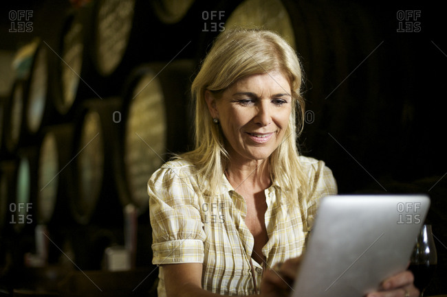 Close up of middle-aged woman holding tablet computer