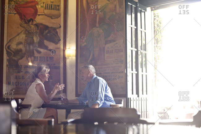 Middle-aged couple talking in a bar