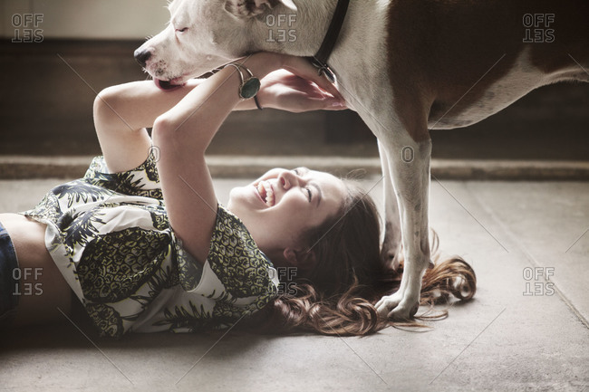 Young woman plays with dog on floor