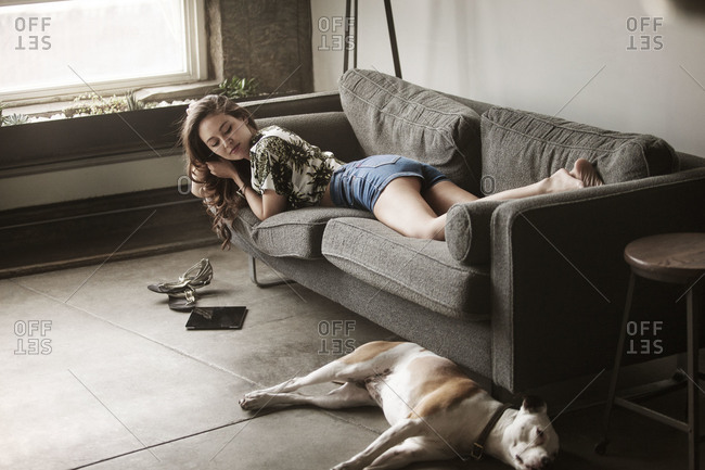 Young woman on couch looks at dog on floor