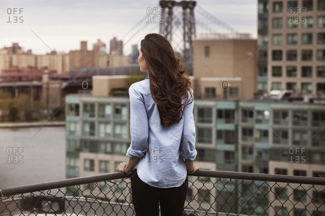 Woman looking over the East River towards Manhattan