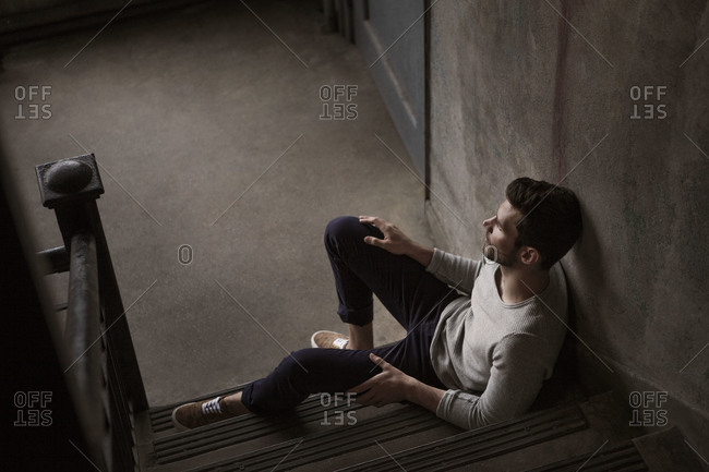 Young man sitting in stairwell