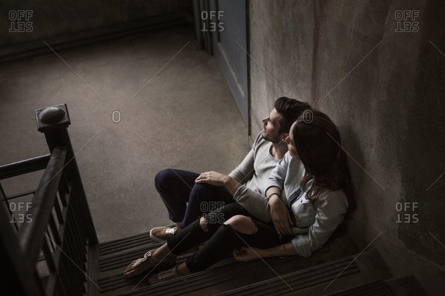 Couple sitting in stairwell