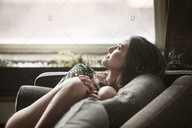 Young woman on couch looking out window