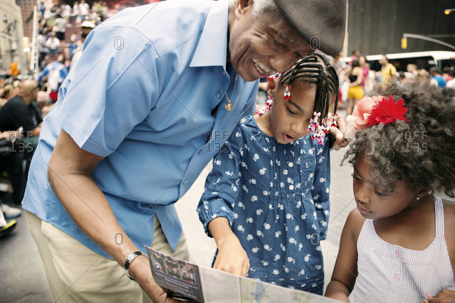 Grandfather showing tourist map to granddaughters, New York