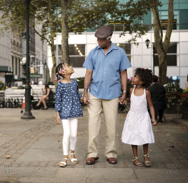 Grandfather holding hands with granddaughters, Bryant Park, New York
