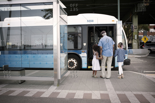 Grandfather taking granddaughters onto the bus, new York