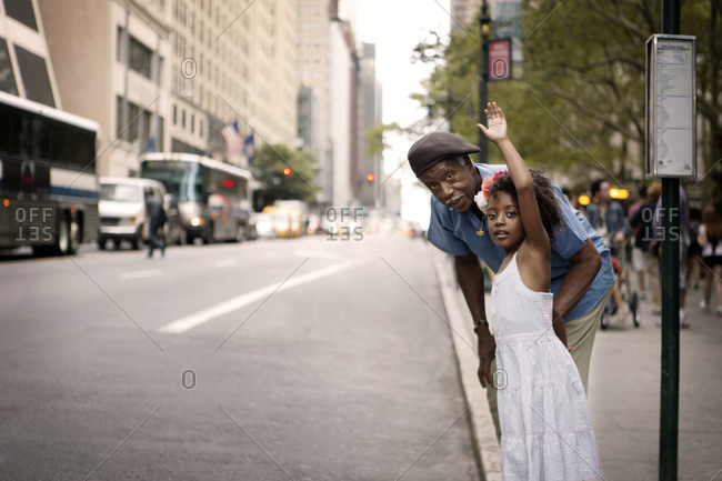 Grandfather with granddaughter who is flagging down a bus, Bryant Park, New York