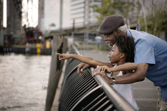 Granddaughter pointing out something to grandfather at the riverfront, New York