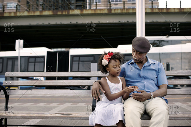 Grandfather listening to granddaughter on park bench, New York