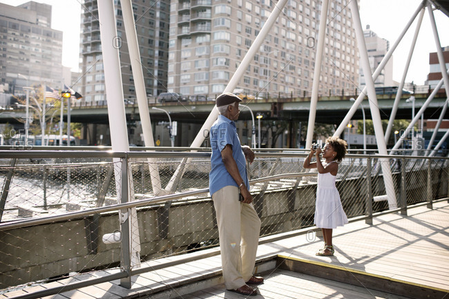 Granddaughter taking grandfather's picture, East River Ferry Terminal, Midtown, Manhattan