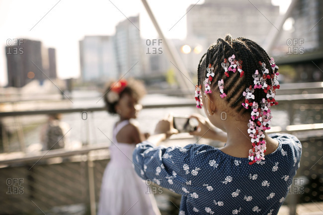 Little girl taking her sister's picture, East River Ferry Terminal, Midtown, Manhattan