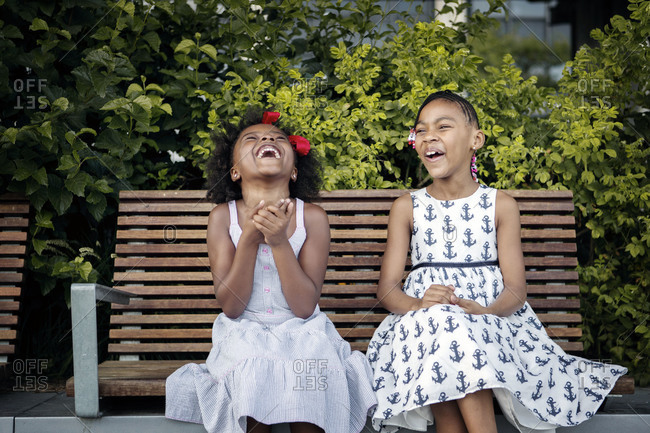 Sisters sitting on a park bench, New York