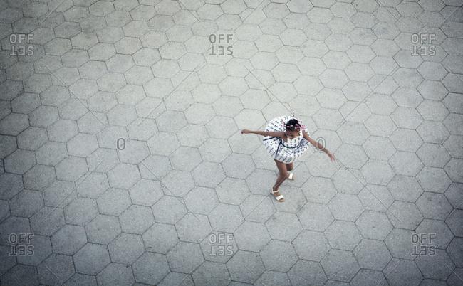 Little girl dancing on the sidewalk, New York