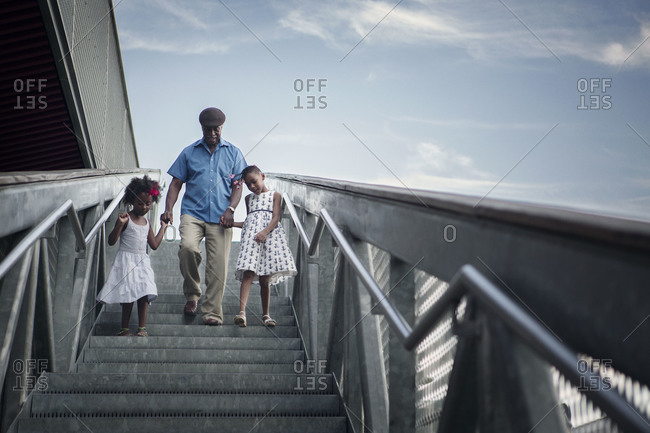 Grandfather walking granddaughters down a staircase, New York