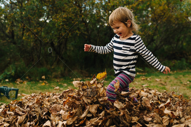 Young girl kicking autumn leaves