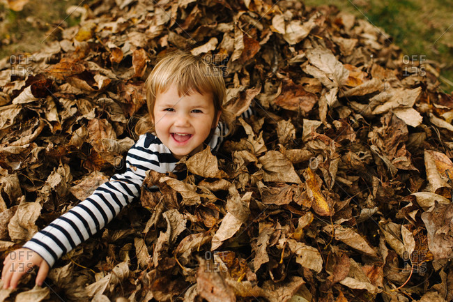 Smiling girl in deep autumn leaves