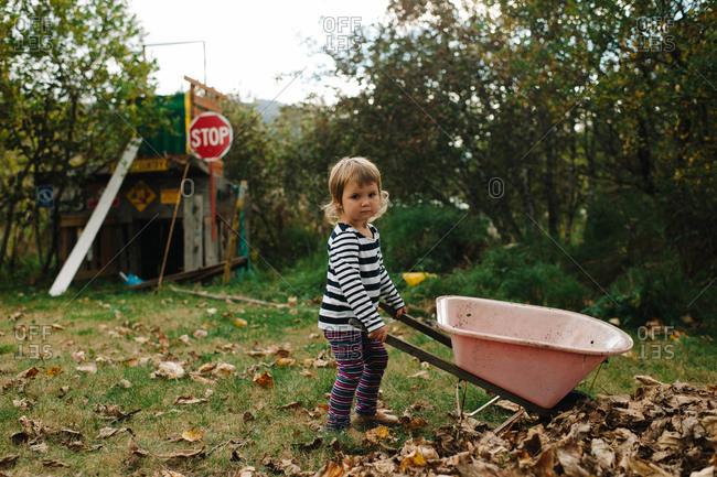 Full length portrait of a little girl with wheelbarrow